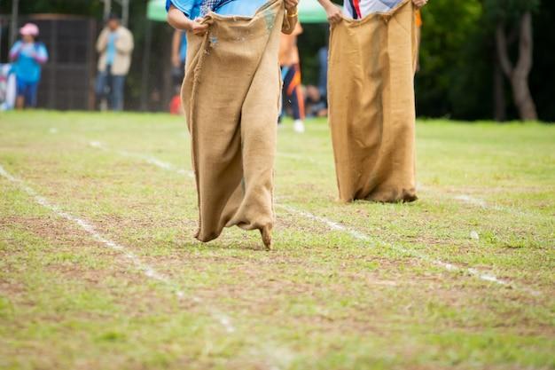 田舎の文化のフィールドで袋レースを実行している人々