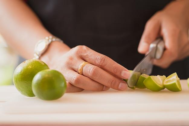 People's hands cutting lemon .