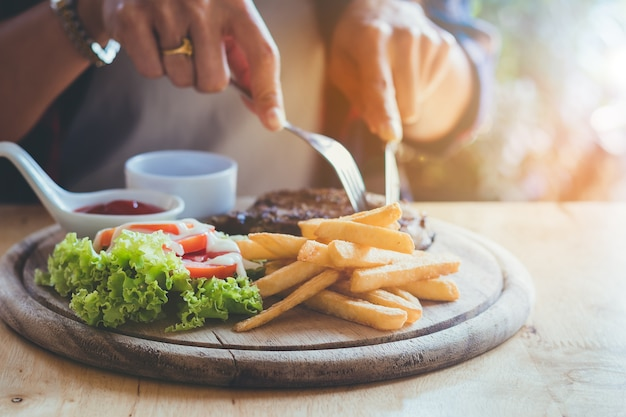 ,people's hands eating delicious steak with fun