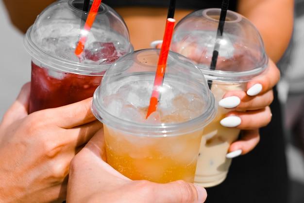 Руки людей держат одноразовые стаканчики со свежим соком, крупным планом. компания людей чокается, выборочный фокус. освежающий напиток