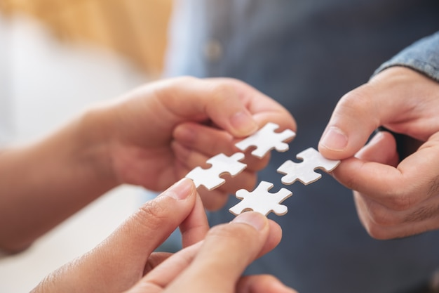 People's hands holding and putting a piece of white jigsaw puzzle together