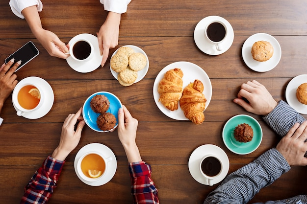 People's hands on wooden table with croissants and coffee.