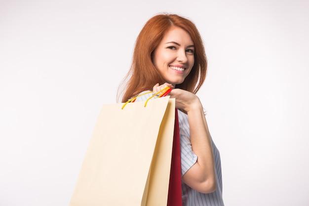 Люди, продажи и концепция консьюмеризма - привлекательная женщина с рыжими волосами над белой поверхностью, держащей хозяйственные сумки.