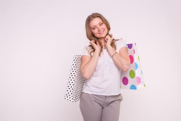 人、販売、消費主義の概念。コピースペースと白の上のショッピング色とりどりのバッグを保持している魅力的な若いブロンドの女性