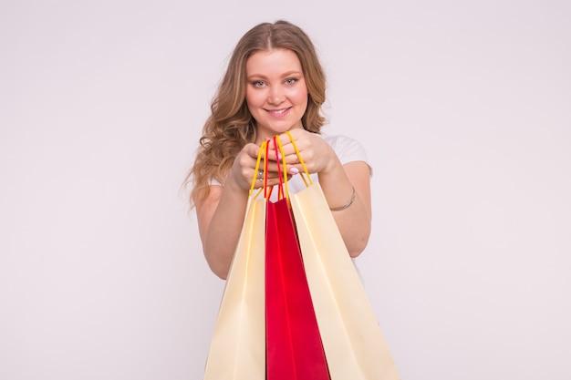 人、販売、消費主義の概念。ショッピングバッグを保持している白の上の美しい女性。