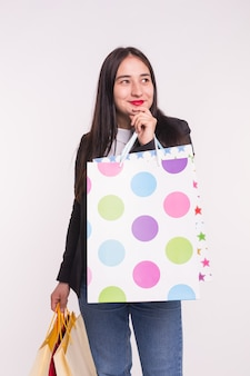 People, sale and consumerism concept. woman dressed in black jacket on white holding shopping multicolored bags.