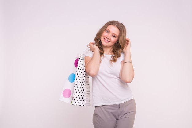 People, sale and consumerism concept. young woman dressed in white t-shirt and grey trousers holding shopping multicolor bags on white
