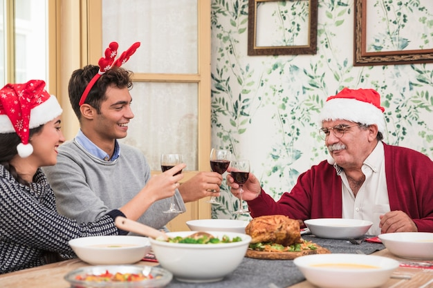 People in santa hats clanging glasses at christmas table