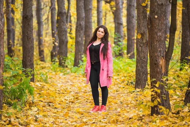 사람, 계절 및 패션 개념-가을에 공원에서 산책하는 플러스 사이즈 여자
