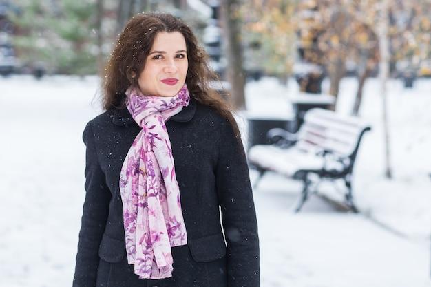 人々、季節、ファッションのコンセプト-冬のストリートでポーズをとるコートの若いブルネットの女性