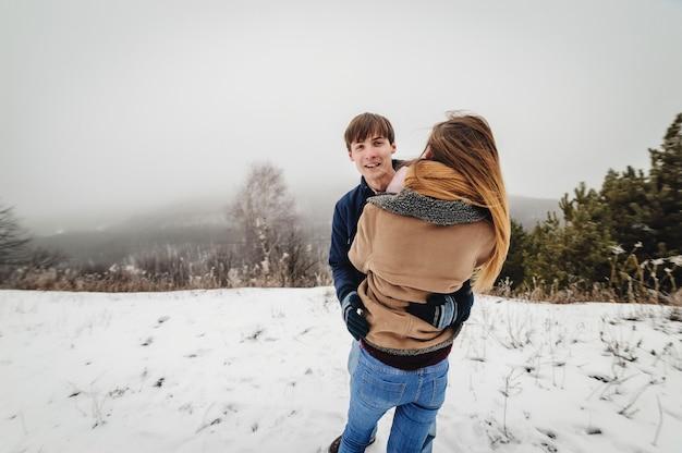 人々、季節、愛とレジャーの概念-冬に屋外で抱き締めて笑う幸せな若いカップル。男と女は雪の公園を歩きます。