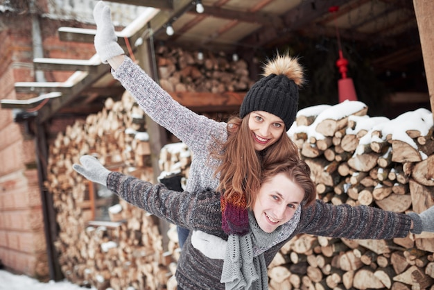 People, season, love and leisure concept - happy couple having fun over winter