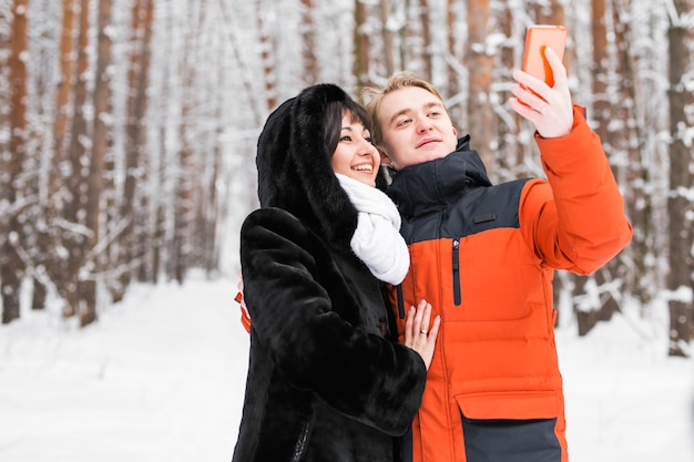 사람, 계절, 사랑, 기술, 여가 개념 - 겨울 배경 위에 스마트폰 셀카봉을 들고 사진을 찍는 행복한 커플