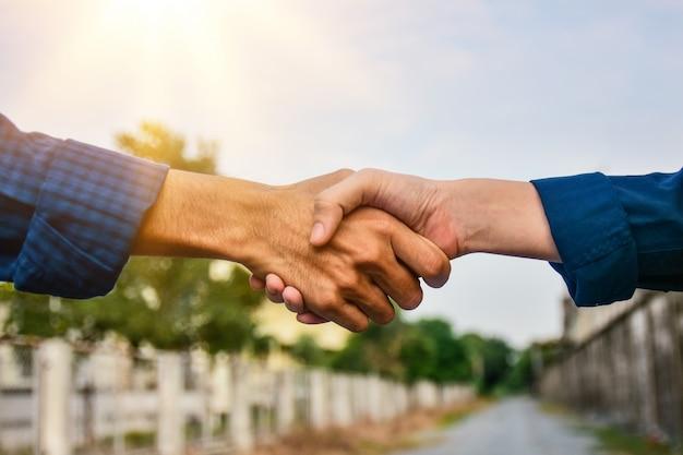 Люди, пожимают руку команде, успех проекта, дрожание рук инженера на улице