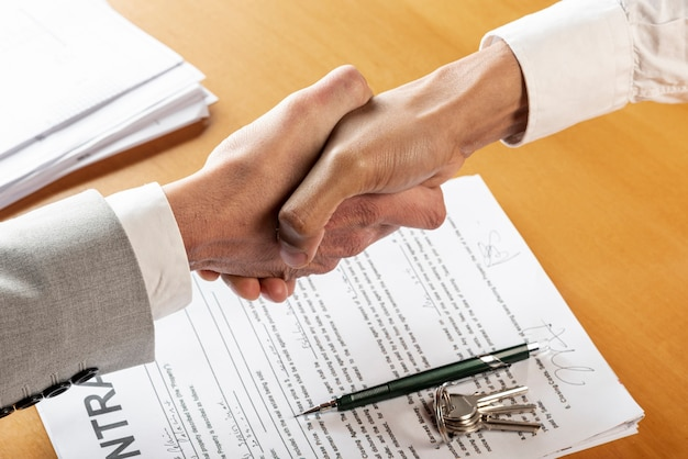 People shaking hands above contract documents