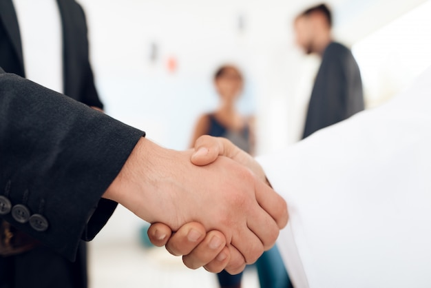 People shaking hands on a white background.