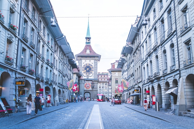 People on the shopping alley with the zytglogge astronomical clock tower of bern in switzerland
