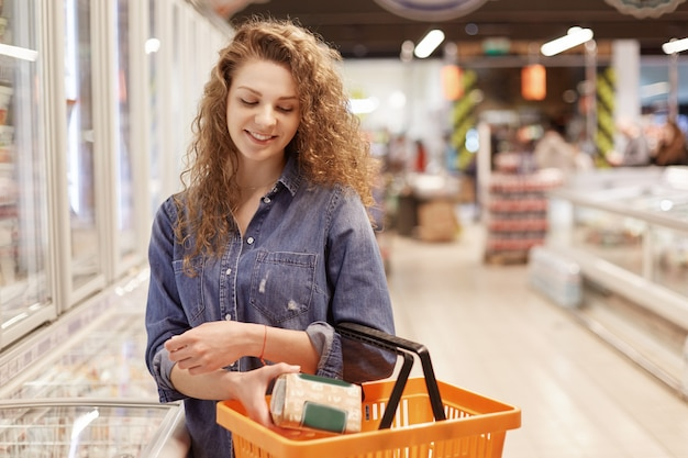 People, shopping and buying concept. adorable beautiful female with curly hair, dressed in fashionable denim jacket, puts product in shopping backet, poses in supermarket with many products.