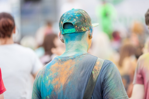 Люди, снятые с обратной стороны, с разноцветной одеждой, окрашенной в яркие цвета, на фестивале красок холи