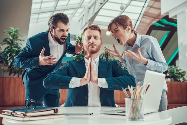 People shout at meditating worker in suit in office.