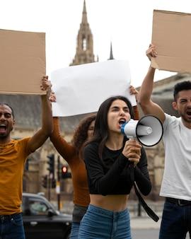 メガホンで抗議して叫ぶ人々がクローズアップ