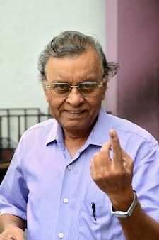 Люди показывают свои помеченные чернилами пальцы после голосования