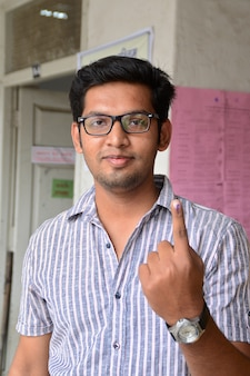People show their ink-marked fingers after casting their votes