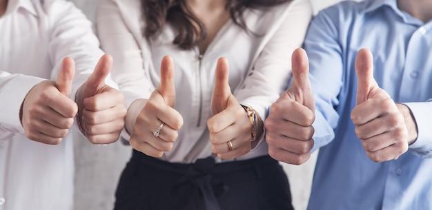親指を立てる兆候を示している人々。チームワーク。戦略。成功