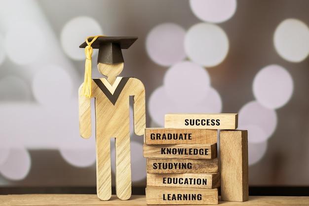Люди подписывают дерево с градацией, празднуя кепку на боке размытия башни деревянных квадратных блоков. прописанная буква, например, образование, выпускник, учиться. идеи для международной образовательной концепции «снова в школу»