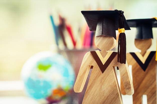 People sign wood with graduation celebrating cap on open textbook with model global map