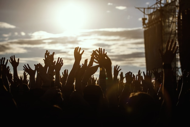 People silhouettes with raised up a human hands