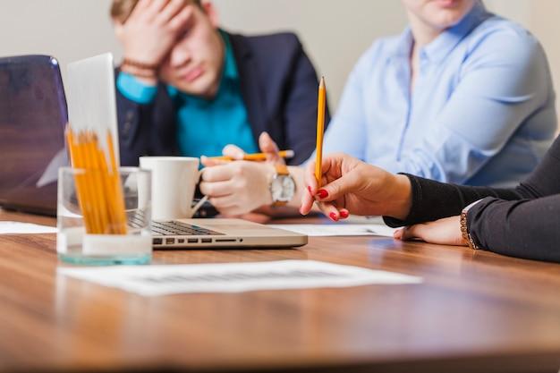 Люди, сидящие на столе, держащие карандаши