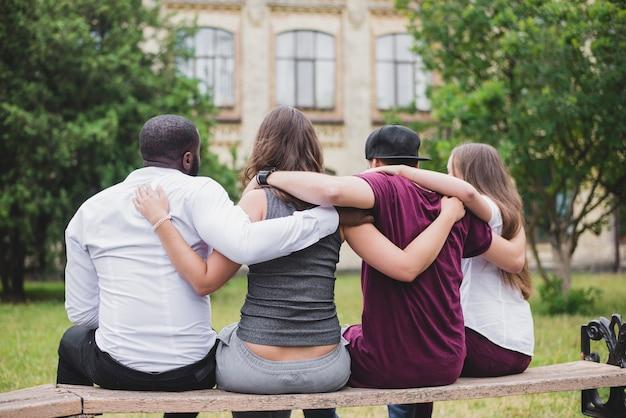 People sitting on bench hugging