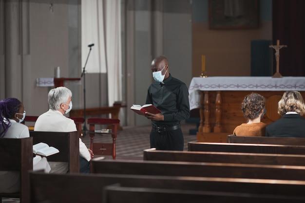 日曜日のミサの間に教会に座って司祭の話を聞いている人々