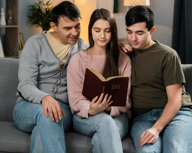 People sitting on the sofa and reading from the bible