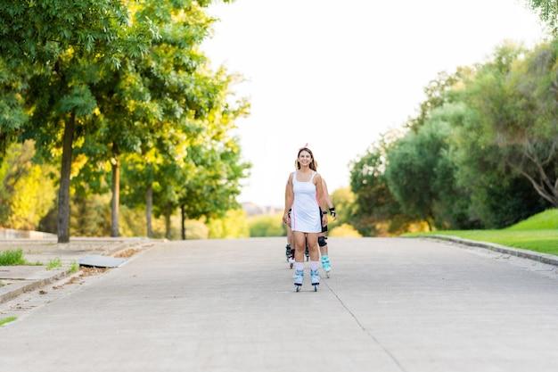 Люди катаются на коньках в очереди посреди улицы в парке