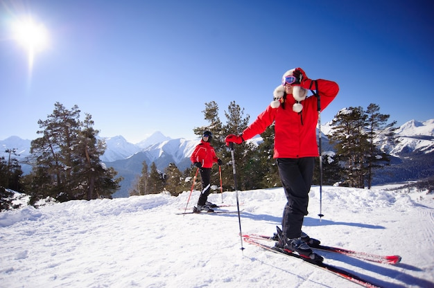 People ski alpine mountains with white snow and blue sky.