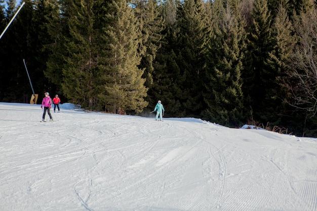 Люди катаются на лыжах на горном склоне