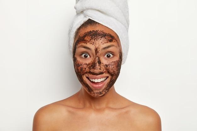 사람, 피부 관리 및 미용 개념. 웃는 어두운 피부의 여성 모델은 커피 스크럽으로 피부를 청소하고 기쁘게 보이며 넓게 웃으며 머리에 수건을 감았습니다.