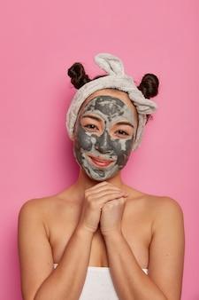人、スキンケア、スパトリートメントのコンセプト。満足している女性モデルは、あごの下に手を保ち、完璧な純粋な肌のためにフェイスマスクを適用し、しわを減らし、新鮮で若く保ち、健康的な衛生状態を保ちます