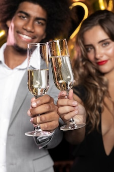 笑顔とシャンパンのクローズアップのメガネを保持している人々