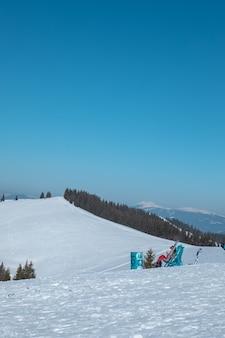 晴れた日の丘の上で休む人々のスノーボーダーとスキーヤー