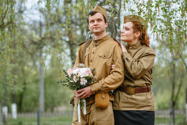 People in soviet military uniforms. a couple stands by a tree