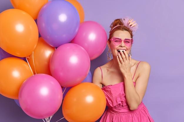 人々の特別な日の休日の気分のコンセプト。陽気なファッショナブルな女性が嬉しそうに口を覆い、サングラスをかけ、お祝いのドレスがカラフルな風船を持っている