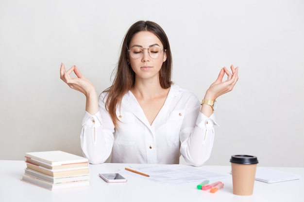 People and spirituality concept. relaxed brunette young woman poses at workplace in mudra sign, enjoys peaceful atmosphere, pull herself together and prepares for work, drinks takeaway coffee