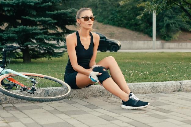 Люди, спорт, 4k, концепция здоровья и образа жизни - подтянутая девушка трогает травмированное колено после дня аварии на велосипеде. девушка защищает колено для велосипедного спуска в замедленном движении. у девушки болит колено