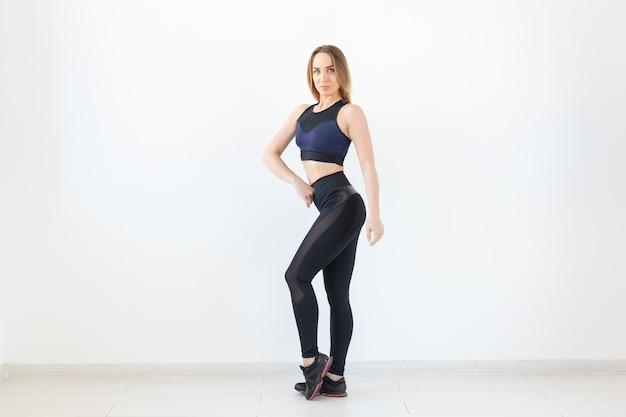 Люди, спорт и фитнес-концепция - привлекательная молодая женщина в спортивной одежде позирует на белом фоне