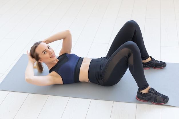 Люди, спорт и фитнес-концепция. молодая женщина фитнеса делает упражнение хруст пресса на полу дома.
