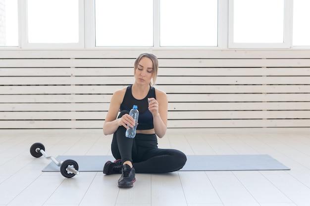 사람, 스포츠 및 피트니스 개념 - 젊은 여성이 매트에 앉아 낚시를 좋아하는 병에서 물을 마십니다.
