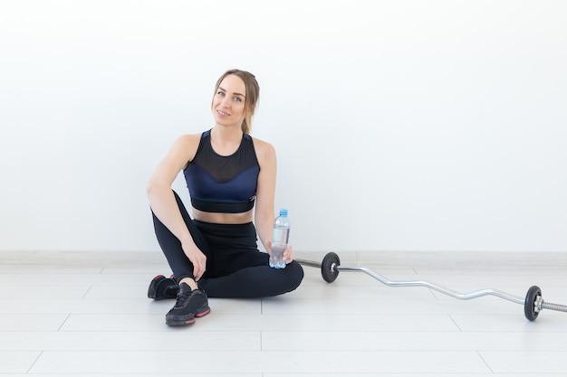 人々、スポーツ、フィットネスのコンセプト-ジムのマットの上に水のボトルと一緒に座っている若い女性。コピースペースのある背景